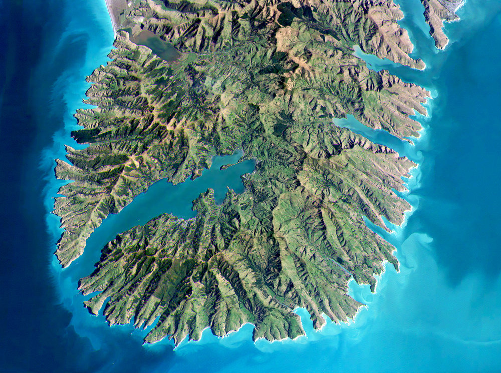 This Overview captures the Banks Peninsula on the east coast of the South Island of New Zealand. The landmass spans an area of approximately 1,150 square kilometres (440 sq mi) and encompasses two large harbours with many smaller bays and coves throughout. Geologically, the peninsula is made up of the eroded remnants of two large shield volcanoes that formed between 8 and 11 million years ago.  -43.7499981, 172.9824904  Source imagery: Axelspace