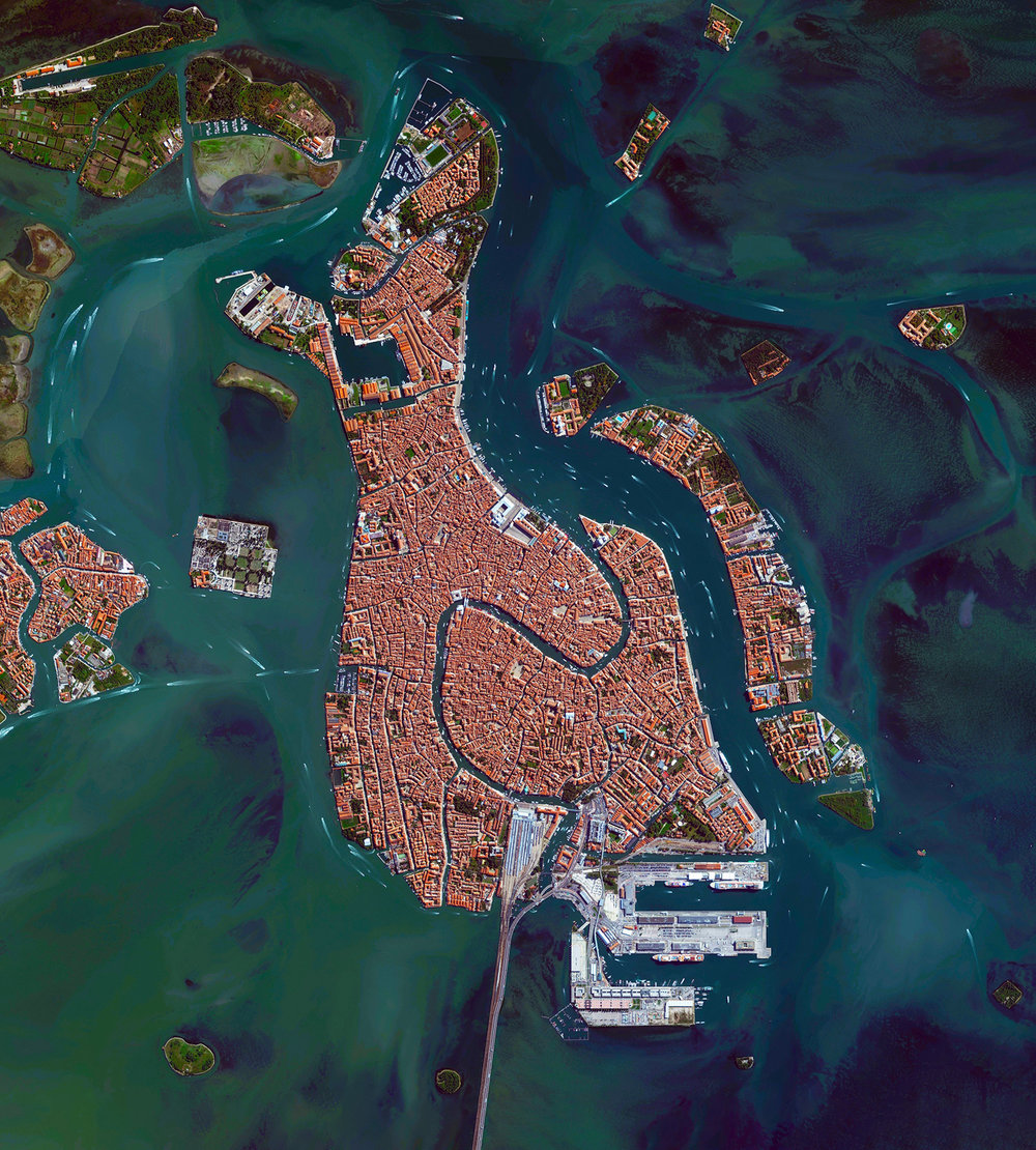 Venice, Italy, is situated upon 118 small islands that are separated by canals and linked by bridges. With tide waters expected to rise to perilous levels in the coming decades, the city has constructed 78 giant steel gates across the three inlets through which water from the Adriatic could surge into Venice's lagoon. The panels — which weigh 300 tons and are 92ft wide and 65ft high — are fixed to massive concrete bases dug into the seabed.  45°26′15″N, 12°20′9″E  Source imagery: DigitalGlobe