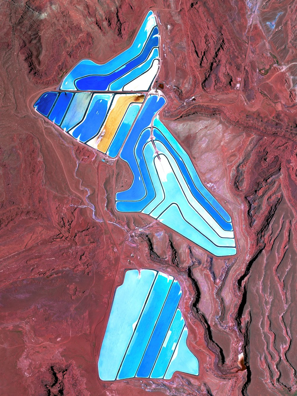 "Evaporation ponds are visible at the Intrepid Potash Mine in Moab, Utah, USA. The mine produces muriate of potash, a potassium-containing salt that is a major component in fertilizers. The salt is pumped to the surface from underground brines and dried in massive solar ponds that vibrantly extend across the landscape. As the water evaporates over the course of 300 days, the salts crystallize out. The blue color seen here occurs because the water is dyed a deep blue to absorb more sunlight and heat, thereby reducing the amount of time it takes for the water to evaporate and the potash to crystallize.  38°29'08.1""N, 109°41'04.6""W  Source imagery: DigitalGlobe"
