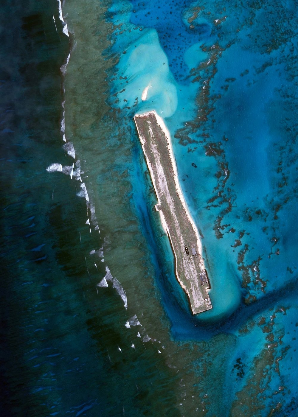 "French Frigate Shoals Airport is a private airfield on Tern Island in French Frigate Shoals, Hawaii. Located roughly 560 miles northwest of Honolulu, the airport has a coral surface that is 3,000 feet long, 200 feet wide, and sits just six feet above sea level. It is owned by the U.S. Fish and Wildlife Service and is only used for emergencies.  23°52'12.5""N, 166°16'58.5""W  Source imagery: DigitalGlobe"