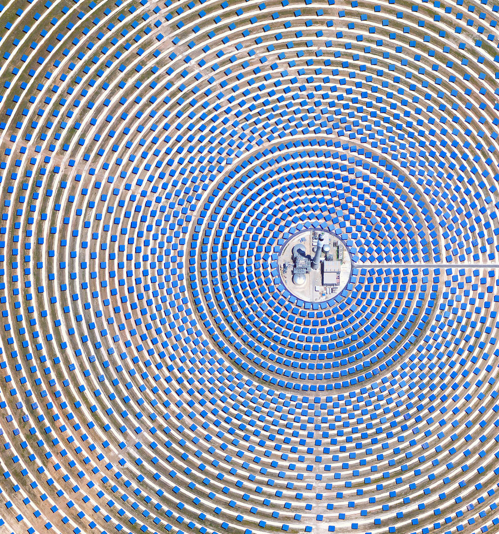 "The Gemasolar Solar Concentrator in Seville, Spain, contains 2,650 heliostat mirrors that focus the sun's thermal energy to heat molten salt flowing through a 460-foot-tall (140m) central tower. The molten salt then circulates from the tower to a storage tank, where it is used to produce steam and generate electricity. In total, the facility displaces approximately 30,000 tonnes of carbon dioxide emissions every year.  37°33'38.0""N, 5°19'53.1""W  Source imagery: DigitalGlobe"