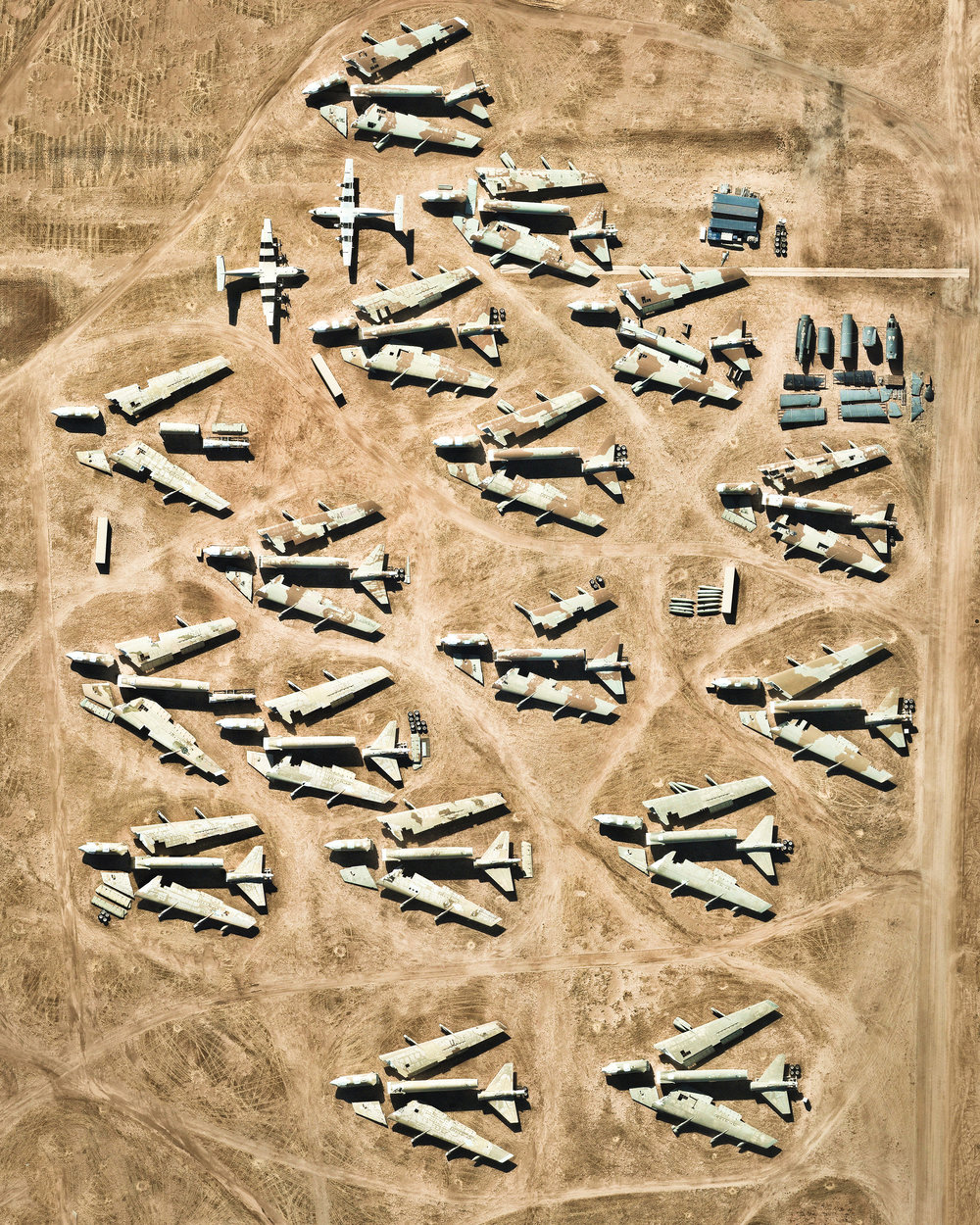"""Disassembled airplanes sit in storage at the Davis-Monthan Air Force Base in Tucson, Arizona. These planes are among more than 4,400 retired American military and government aircraft being stored and preserved on-site by the 309th Aerospace Maintenance and Regeneration Group. Covering more than four square miles (10.5 km sq.), this facility is the largest of its kind in the world.  32°08'57.1""""N, 110°49'58.1""""W  Source imagery: Nearmap"""