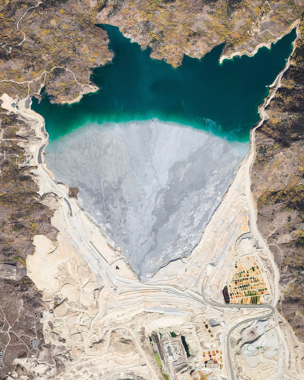 """The Yankee Doodle Tailings Pond in Butte, Montana, is used as a dumping site for leftover materials from nearby copper mines. It covers an area of roughly 2.5 square miles (6.5 sq. km) and is contained by a 650-foot (200 m) tall earthen dam — one of the largest of its kind in the United States. To help offset the acidity of mine waste, lime rock is added to create a non-acidic tailings slurry.  46°02'37.3""""N, 112°30'23.2""""W  Source imagery: DigitalGlobe"""