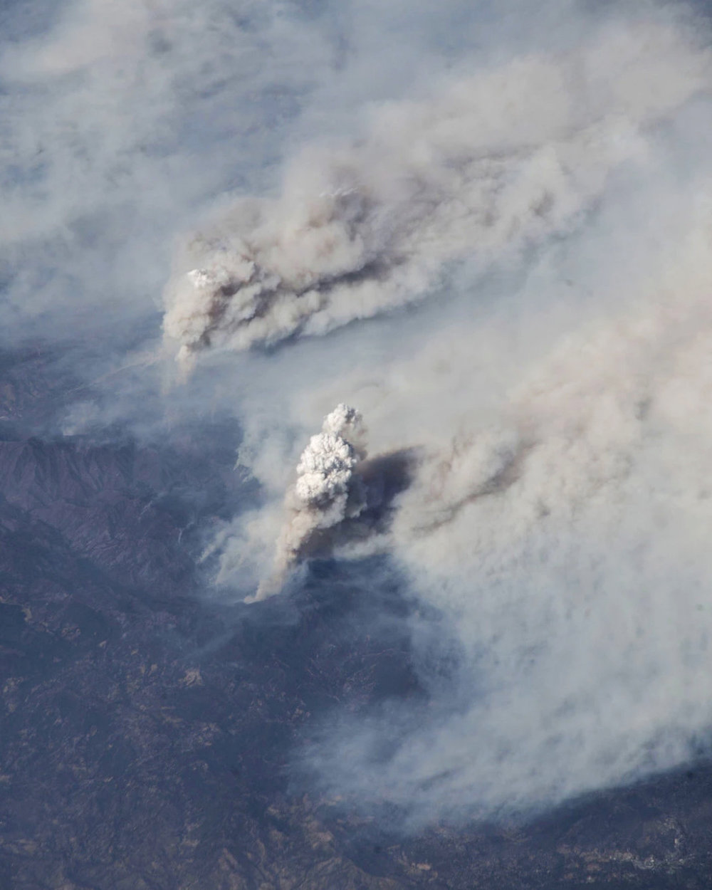 This image of the Carr and Ferguson wildfires in California was taken aboard the International Space Station by European Space Agency astronaut Alexander Gerst on August 3rd. The Carr Fire, which was first reported July 23rd, has burned more than 261 square miles (676 sq. km) in Shasta and Trinity counties and is currently the sixth-most destructive fire in California's history. The Ferguson Fire began July 13th and has since burned 147 square miles (382 sq. km) in the Sierra and Stanislaus National Forests. Both fires have been attributed to warming temperatures and unprecedented dryness.  Source imagery: NASA - National Aeronautics and Space Administration