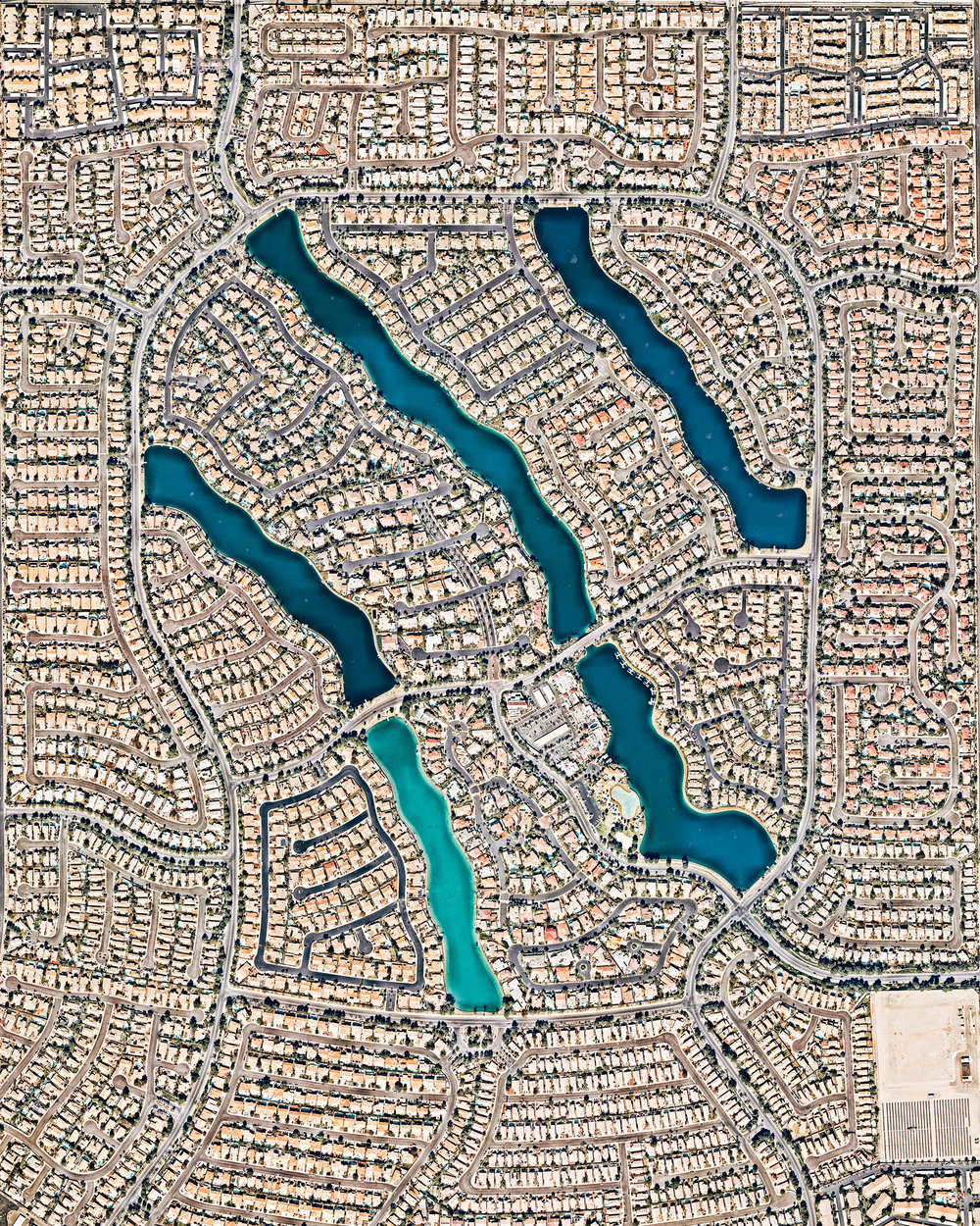 "Desert Shores is a 682-acre master planned community in northwest Las Vegas, Nevada. Constructed in 1988, it has more than 3,300 housing units ranging from condominiums to large, custom-built homes. At the center of Desert Shores are four man-made lakes, the largest of which — Lake Jacqueline — is flanked by the other three.  36°12'43.9""N, 115°16'08.1""W  Source imagery: Nearmap"