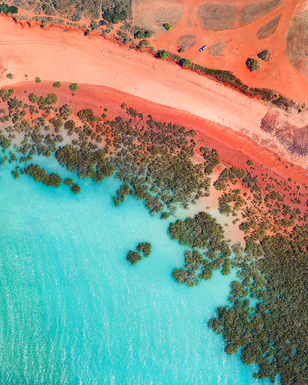 """The aquamarine water of Roebuck Bay rolls onto red sand in Broome, Western Australia. A coastal town, Broome is home to roughly 14,000 people, but its population can grow to upwards of 45,000 per month during peak tourist season from June to August.  17°58'09.8""""S, 122°14'16.3""""E  Source imagery: Nearmap"""