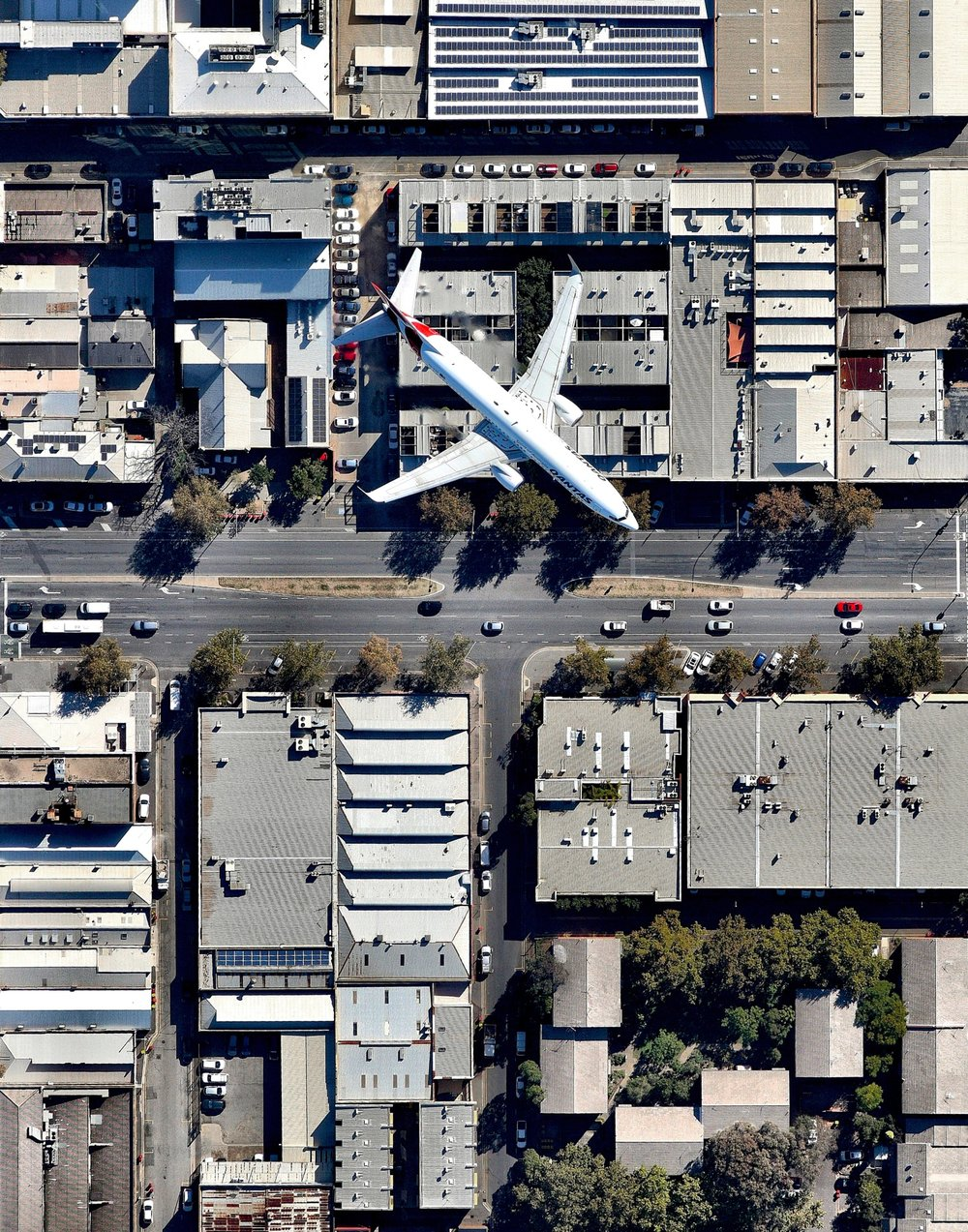 """A Qantas jet flies over Wakefield Street in Adelaide, South Australia, after taking off from Adelaide Airport. Adelaide is the fifth-largest city in Australia, and its airport is the country's fifth-busiest. Between 2016 and 2017, it served roughly 8 million passengers and saw an 11% increase in international travelers.  34°55'41.2""""S, 138°36'25.5""""E  Source imagery: Nearmap"""