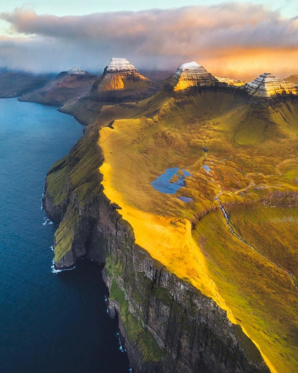 "Check out this amazing shot we found on Drone Of The Day, which captures Cape Enniberg, the northernmost point of the Faroe Islands. At 2,474 feet (754 m) high, Cape Enniberg is one of the highest promontories in the world. Throughout the summer, boat tours stop at Cape Enniberg to give tourists an up-close view of the massive cliff and the famous bird colony found there.  62°23'00.0""N, 6°34'00.0""W  Source imagery: Karl 'Shakur' Ndieli"