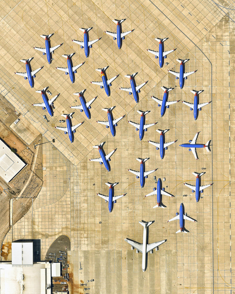 "In this Overview, 25 airplanes are parked in a cluster at the Southern California Logistics Airport in Victorville, California. Also known as Victorville Airport, it is home to Southern California Aviation, a large transitional facility for commercial aircraft. No commercial passenger services are offered at the airport except for fixed-based operator and charter flights.  34°35'51.0""N, 117°22'59.0""W  Source imagery: Nearmap"