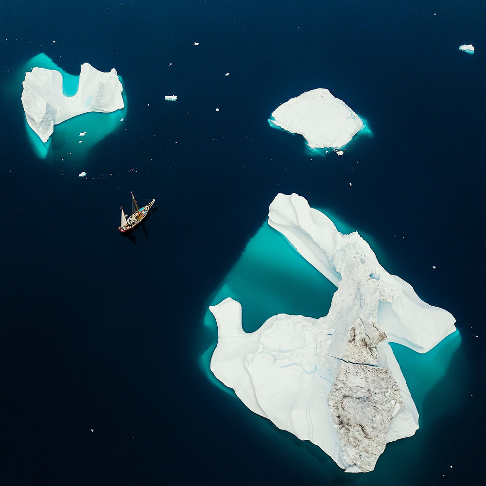 "A sailboat cruises through a group of massive icebergs offshore Tiniteqilaaq, a small settlement in southeastern Greenland. Also known as Tiilerilaaq, the village has a population of just 134 people and is rather difficult to access, except by helicopter.  65°53'20.0""N, 37°46'45.0""W  Source imagery: Christopher Michel Photography"