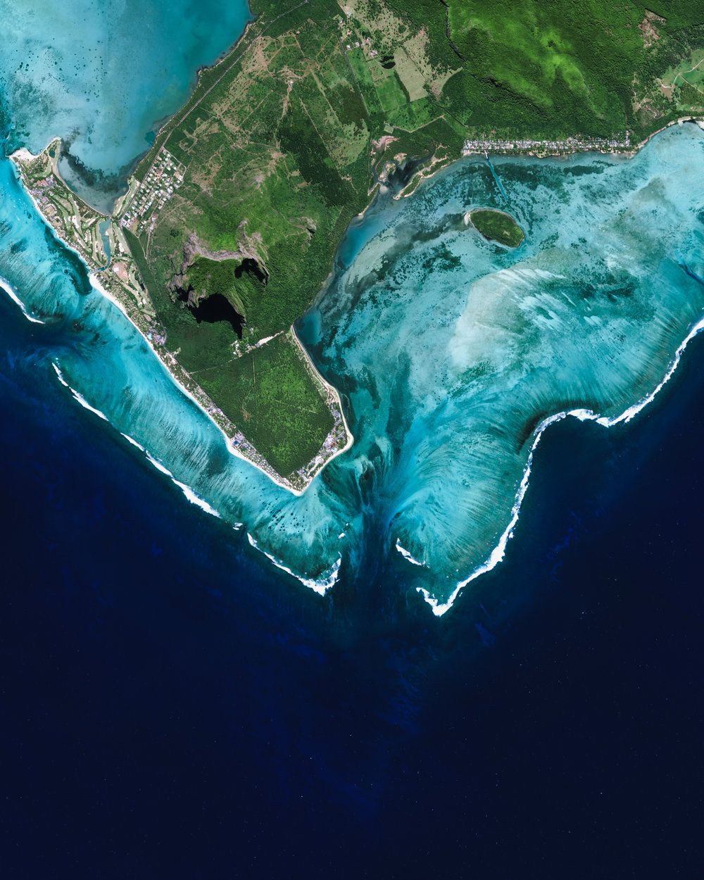 "Just off the southwestern corner of Mauritius (shown at the center of this Overview) is what appears to be an underwater waterfall. In reality, it is just the flow of underwater currents and sand patterns on the ocean floor that form this spectacular optical illusion from the aerial perspective. Mauritius is an island nation in the Indian Ocean, roughly 1,200 miles (2,000 km) off the southeastern coast of Africa.  20°28'23.9""S, 57°18'33.3""E  Source imagery: DigitalGlobe"