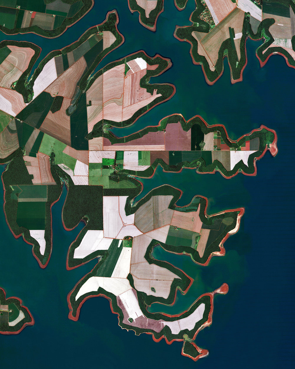 "Agricultural fields line the shores of the Itaipu Reservoir — a body of water that forms the border between Brazil and Paraguay. The area's tropical climate makes it an ideal place to grow sugarcane, coffee, tea, and cotton.  25°18'20.3""S, 54°25'12.6""W  Source imagery: DigitalGlobe"