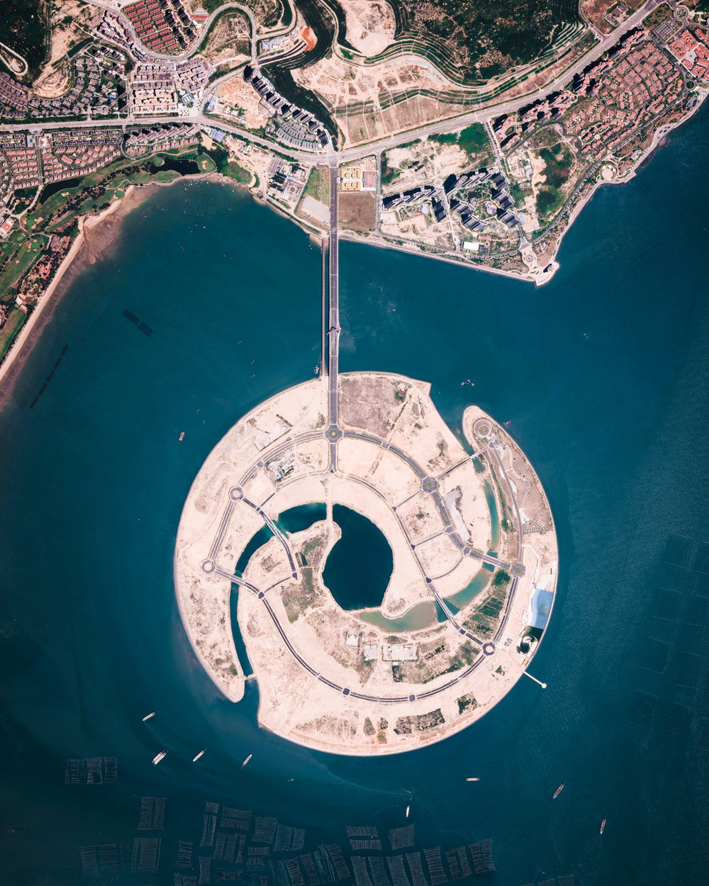 "Shuangyu Island, also known as Double Fish Island, is a man-made island under construction in Xiamen Bay, Southeast China. Its design, which depicts a pair of dolphins circling each other, calls for roughly 8.8 billion gallons (33.3 billion liters) of reclaimed land to create. The island is slightly more than one mile (1.68 km) in diameter with about 7 miles (11.4 km) of coastline. When finished, it will house a high-end ecological resort.  24°22'28.7""N, 118°03'47.3""E  Source imagery: DigitalGlobe"