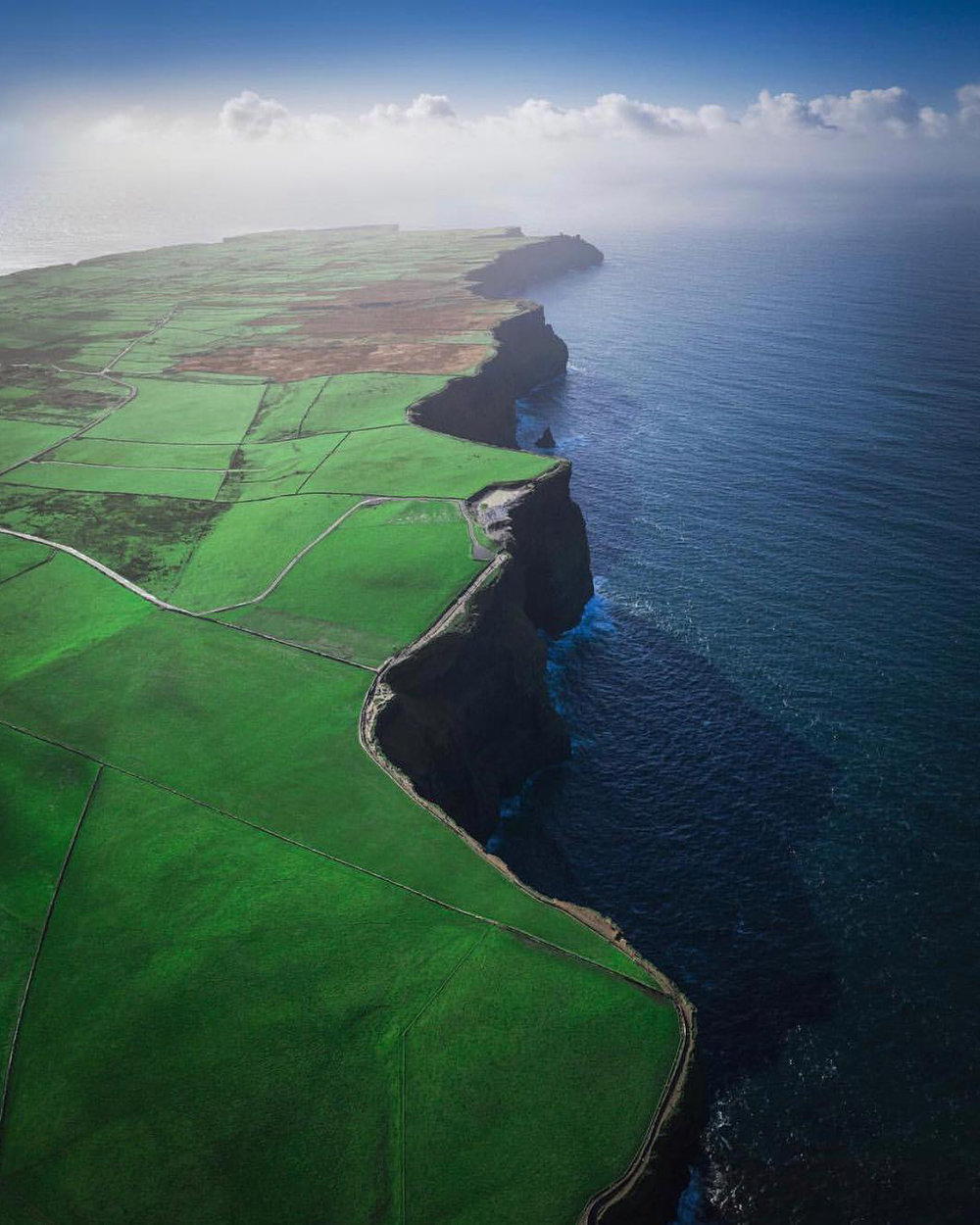 """Happy St. Patrick's Day! Here's an incredible aerial view of the Cliffs of Moher, which stretch for about 8.7 miles (14km) along the Atlantic Ocean in County Clare, Ireland. The cliffs range in height from 390 feet (120m) to 702 feet (214m) and are among the most visited tourist sites in Ireland, with about 1.5 million visitors a year.  52°58'18.3""""N, 9°25'34.8""""W  Source imagery: Max Malloy Photography"""