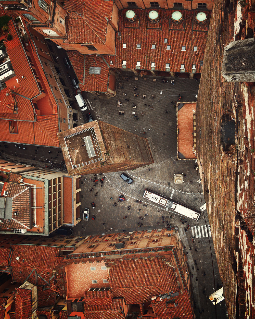 """Check out this aerial view of Bologna, Italy, taken atop Asinelli Tower. This tower was constructed between 1109 and 1119 and is the most prominent of the medieval """"Towers of Bologna,"""" at 319 feet (97.2 m) tall. Its companion tower, the Garisenda, can be seen at the center of the courtyard and is roughly 157 feet (48 m) tall.  44°29'39.5""""N, 11°20'48.5""""E  Source imagery: @bogdandada"""