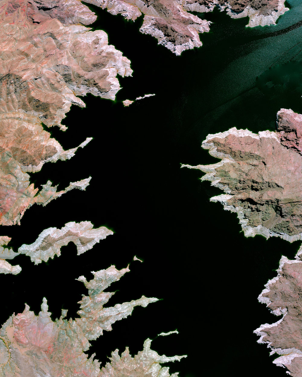 """Lake Mead — located on the Colorado River 24 miles (38 km) southeast of Las Vegas, Nevada — is the largest reservoir in the United States. The lake was formed with the creation of the Hoover Dam in the 1930s. Due to a combination of drought and increased water demand in the surrounding states (specifically California, Nevada, New Mexico, and Arizona) the lake's water level has been lowering drastically in recent years. This decreasing water level exposes the white shoreline that is visible in this Overview.  36°15'00.0""""N, 114°23'24.0""""W  Source imagery: DigitalGlobe"""