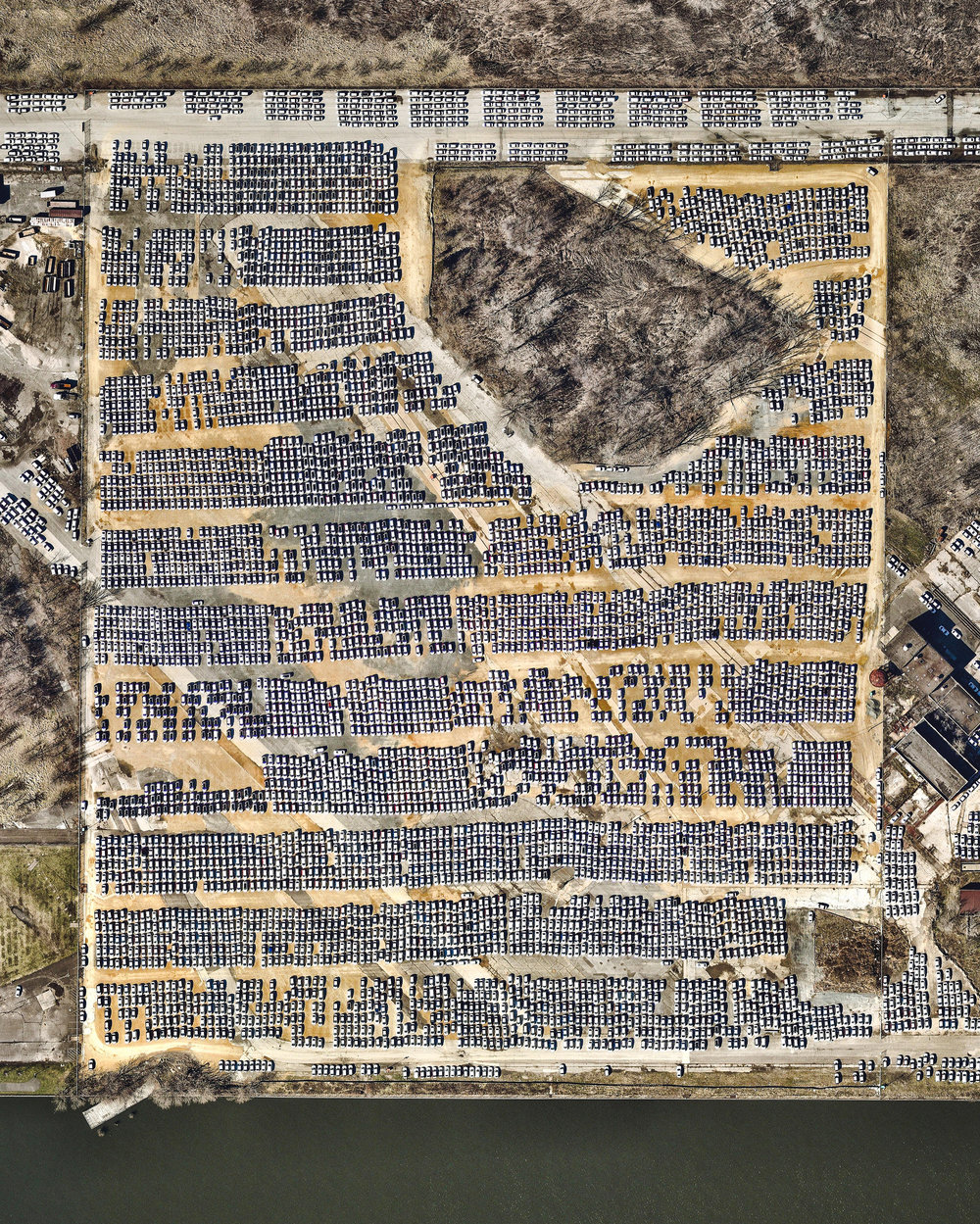 """Thousands of automobiles fill a large lot near the Philadelphia Navy Yard in southern Philadelphia, Pennsylvania. Since 2010, when Hyundai and Kia Motors moved their import businesses to the city, several large lots like this have popped up to accommodate an influx of new vehicles. At least 120,000 vehicles a year have arrived at the Port of Philadelphia since 2011, and more than 155,000 were delivered in 2015.  39°53'25.0""""N, 75°09'20.8""""W  Source imagery: Nearmap"""