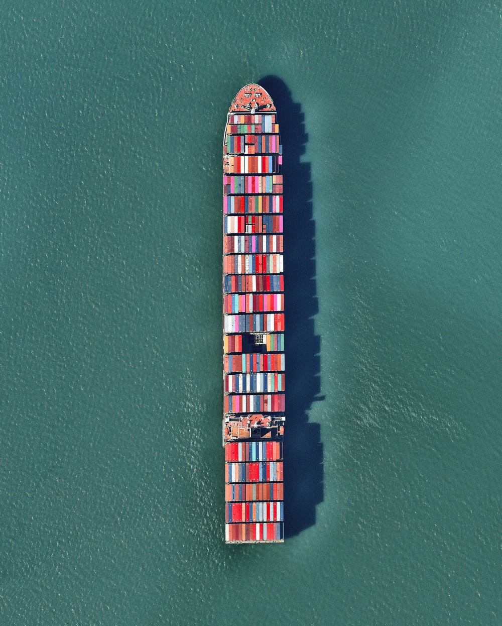 """A ship full of containerized cargo navigates San Francisco Bay, located between San Francisco and Oakland, California. Due to San Francisco's limited real estate, Oakland has served as the primary Bay Area port since the 1960s. The Port of San Francisco handled no containerized cargo in 2017, whereas the Port of Oakland had a throughput of nearly 2.5 million twenty-foot equivalent units (TEUs) that year.  37°46'01.3""""N, 122°20'58.3""""W  Source imagery: Nearmap"""