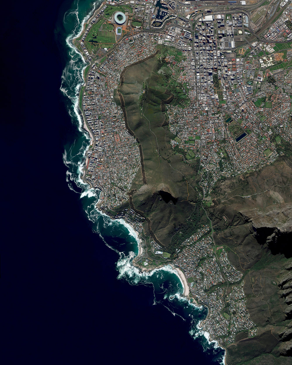 """Cape Town is a port city on South Africa's southwest coast. The city's geography is influenced by the surrounding Table Mountain, the Durbanville Hills, and the expansive lowland region known as the Cape Flats. These geographic features divide the city into several commonly known suburbs, many of which developed simultaneously and share common attributes of language and culture. This unique blend has made Cape Town one of the most multicultural cities in the world, attracting tourists, immigrants, and expats to South Africa.  33°55'31.0""""S, 18°25'26.0""""E  Source imagery: DigitalGlobe"""