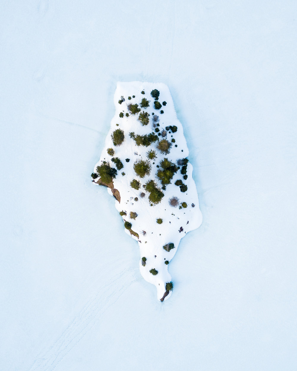 """Patches of vegetation poke through a snow-covered island on Gold Creek Pond, located in Kittitas County, Washington. During the 1970s, the pond and surrounding areas were one large gravel pit, which construction workers used in building the nearby Interstate 90 highway. The site was cleaned up in the early 1980s, revealing a picturesque mountain pond that is now surrounded by a popular hiking loop.  47°23'58.8""""N, 121°22'43.7""""W  Source imagery: John Westrock (@only_westrock)"""