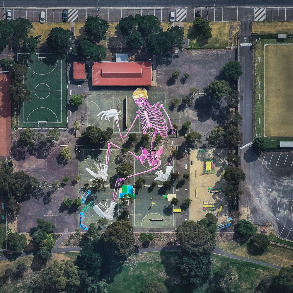 """A mural of a pink skeleton covers the grounds at Reservoir Skatepark in northern Melbourne, Australia. This piece spans roughly 20,000 square feet (1,858 sq. m) and is one of many large murals in the area created by local artist Kitt Bennett. For a sense of scale, 20,000 square feet is nearly half the size of an American football field.  37°42'42.6""""S, 144°59'33.1""""E  Source imagery: Nearmap"""