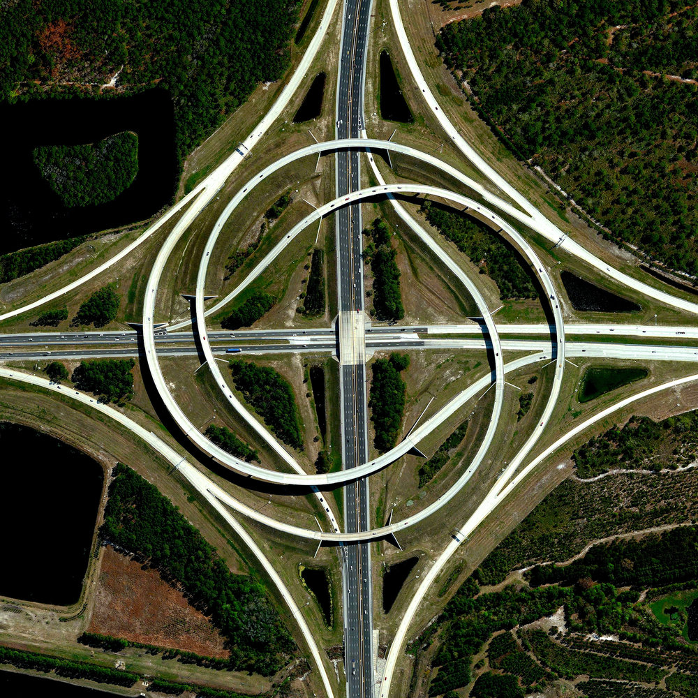 """A turbine interchange connects the SR 9A and SR 202 in Jacksonville, Florida, USA. Also known as a whirlpool interchange, this structure consists of left-turning ramps sweeping around a center interchange, thereby creating a spiral pattern of right-hand traffic. This type of junction is rarely built, due to the vast amount land that is required to construct the sweeping roads.  30°15'11.0""""N 81°30'58.3""""W  Source imagery: DigitalGlobe"""