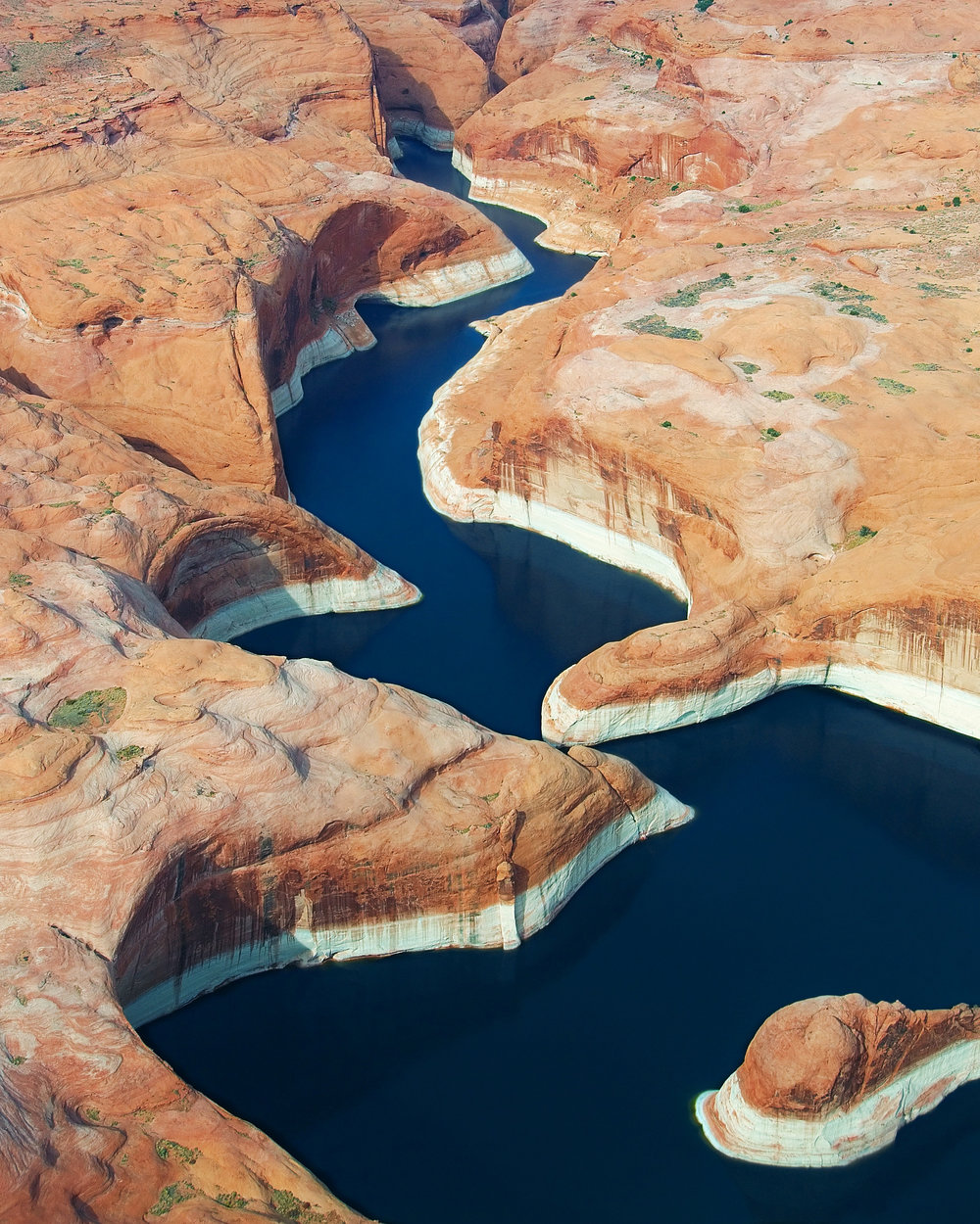"""Lake Powell is a reservoir on the Colorado River, straddling the border between Utah and Arizona, USA. Behind Lake Mead, it is the second largest man-made reservoir by volume in the country, capable of storing 7.9 trillion gallons (29.9 trillion liters) of water when full. Water levels on the Colorado River have been below average since 2000, made evident by the light-colored layer of rock just above Lake Powell's surface.  37°04'21.8""""N 111°13'55.0""""W  Source imagery: Rainer Krienke"""