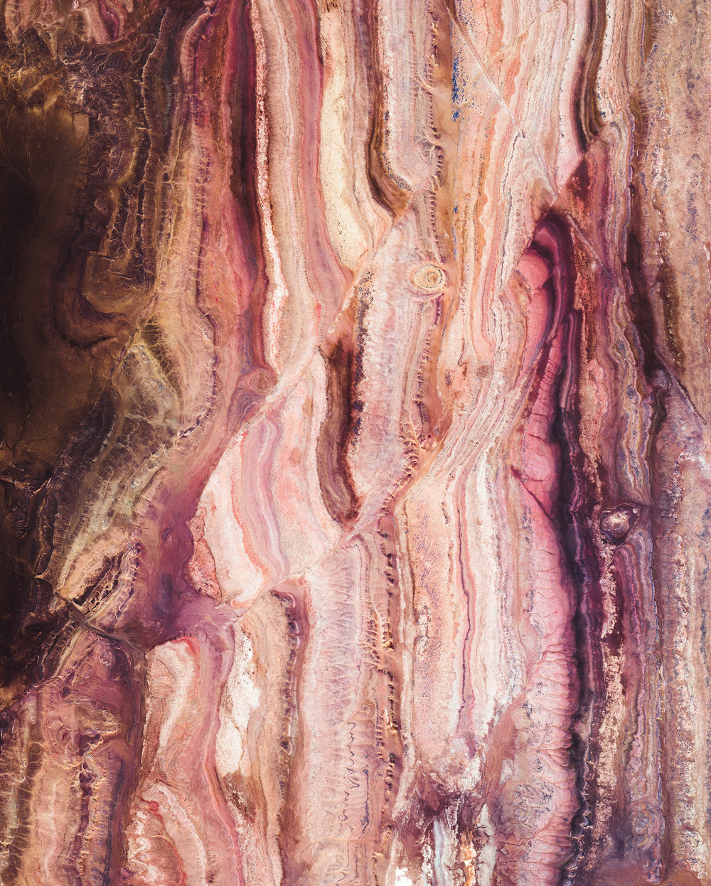 """This Overview shows colorful rock formations in the Sahara Desert, west of the town of Reggane, Algeria. The climate in this region is torrid and almost rainless, with an average annual rainfall of less than 0.4 inches (10 mm). In the summer, daytime temperatures are known to consistently reach 122°F (50°C), earning this area its nickname — the """"triangle of fire.""""  25°11'32.6""""N 3°23'21.3""""W  Source imagery: Maxar Technologies"""