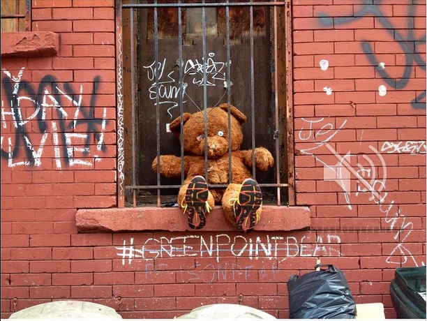 A stuffed bear dubbed the Greenpoint Bear sits with one eyeball behind bars in Greenpoint, NY (Photo by Bailey Constas)
