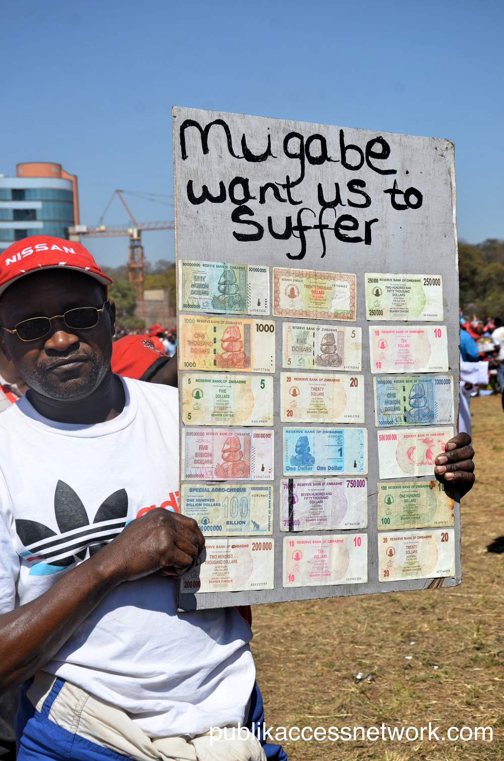 A man holding a Zimbabwean dollar 'mosaic' reminiscent of the pre2009 hyper inflation.