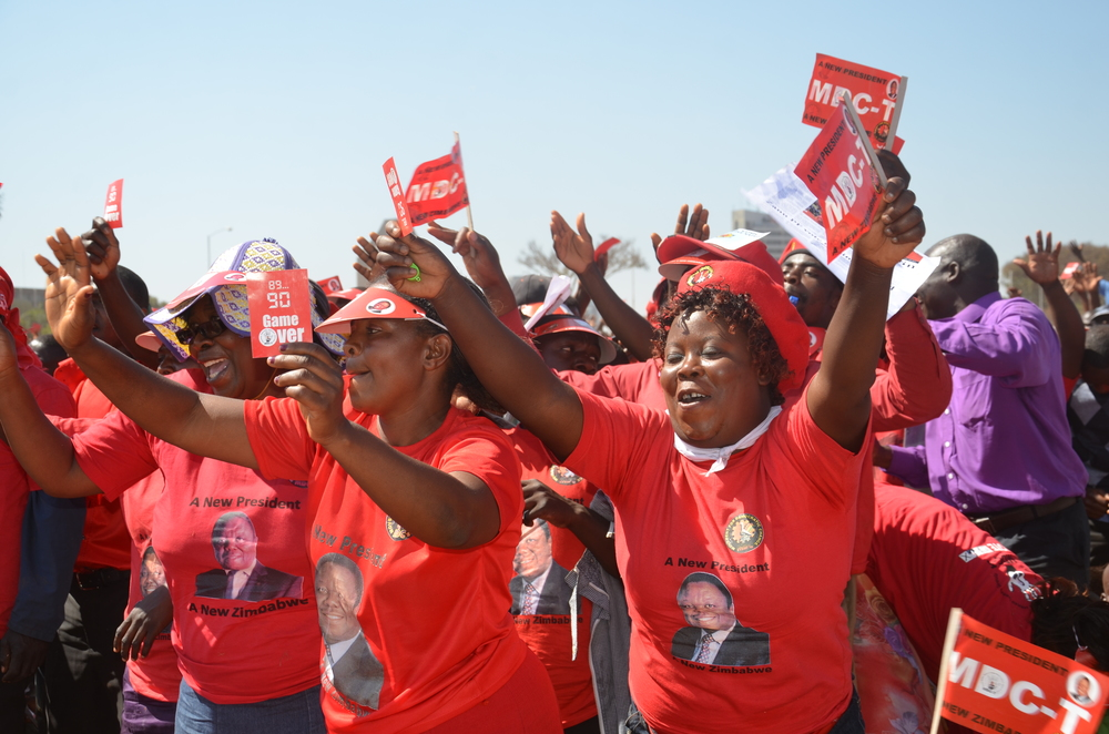 MDC supporters waving 'game over' red cards showing 90 minutes of full-time soccer match which by coincidence was President Mugabe's age then.