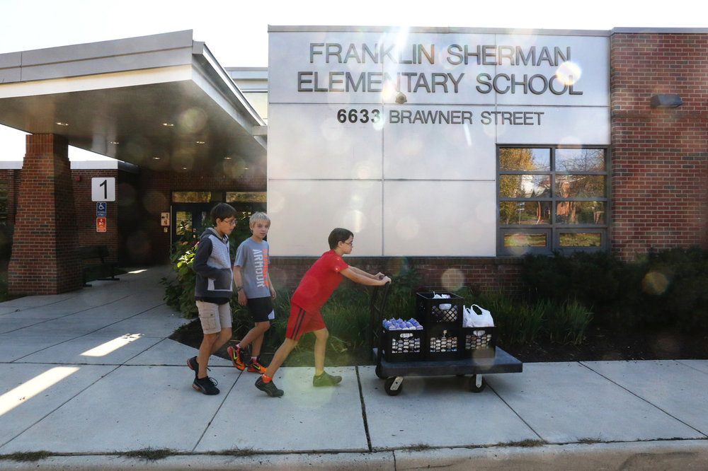 Franklin Sherman Elementary students Nicola Hopper, 11, Jake Hensley, 11, and Aya Hopper, 10, transport collected food from their school to McLean Baptist Church, located across the street from the school. Victoria Milko/NPR