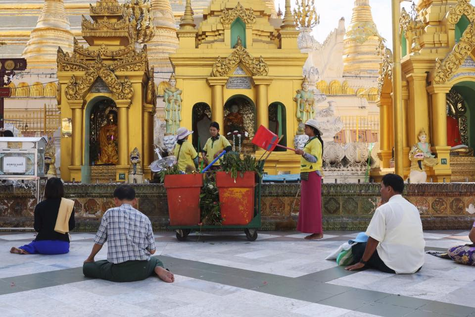Workers at Shwedagon Pagoda throw away offerings left by visitors. January 2017.