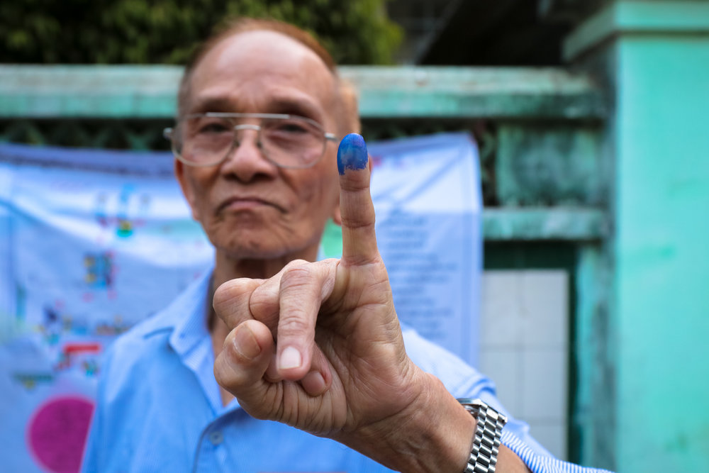 A man shows the tell-tale ink mark that shows he has voted. Yangon.