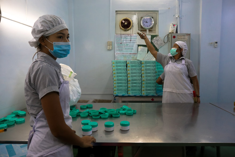 Keepin' cool. Thanaka factory workers pack and seal jars of ready-made thanaka to be shipped across the country.