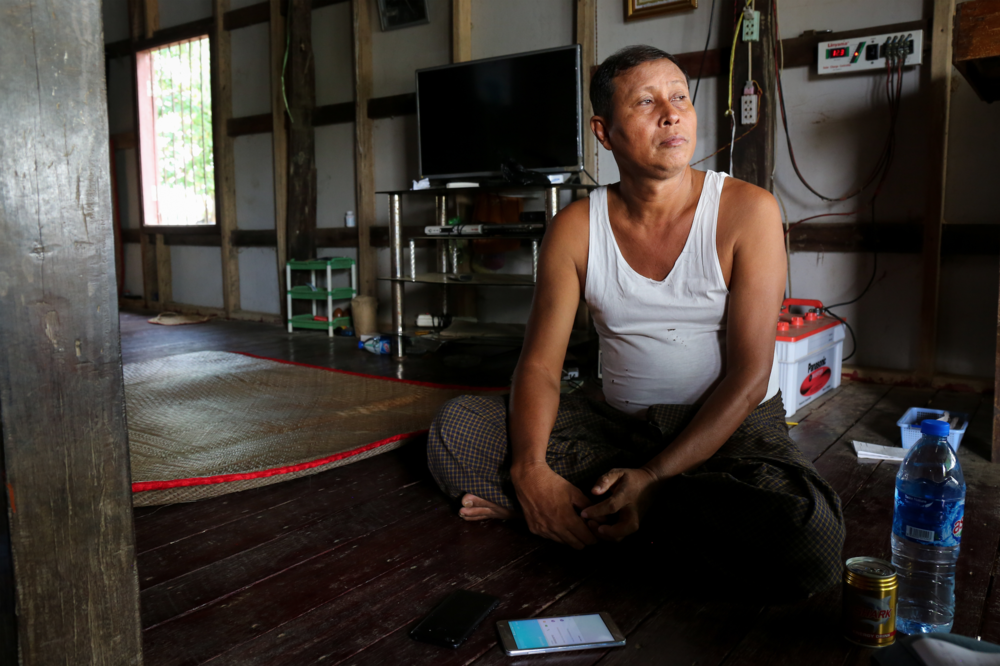 A cyclone survivor sits in his home, describing life then and now. Irrawaddy Division, Myanmar.