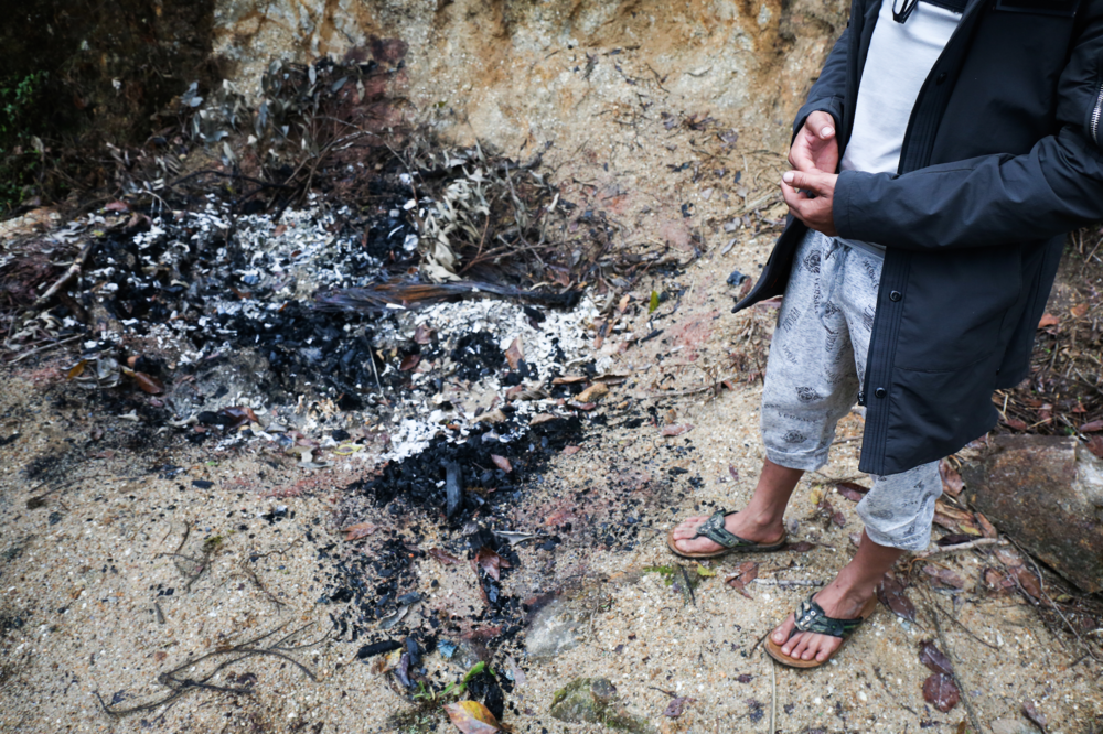 A brother of one of the slain medics stands next to the charred remains of the women. The Burmese military threw the bodies into a shallow grave on the side of a mountain, which days later was discovered by local villagers. August 2018.