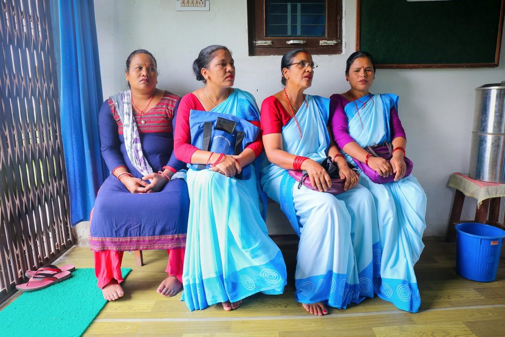 Female health workers sit in a clinic during their monthly meeting. Nepal, August 2018.