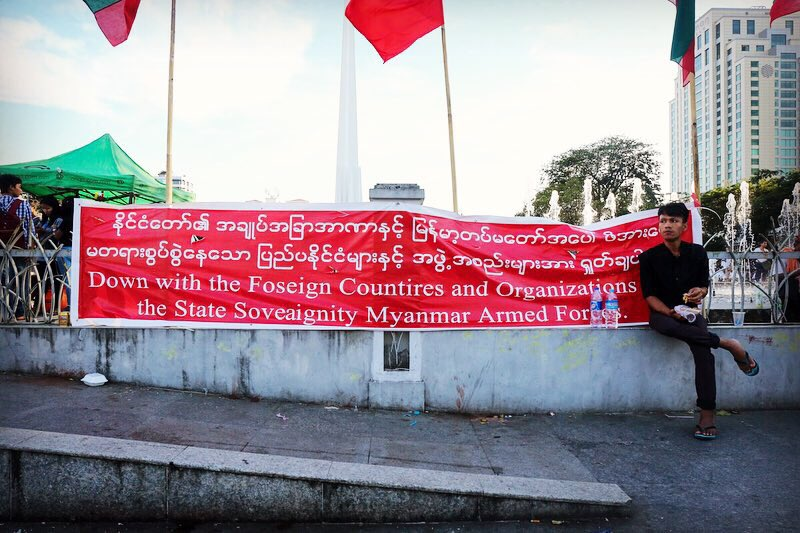A man sits in-front of a banner hung my pro-military nationalists during the demonstration.
