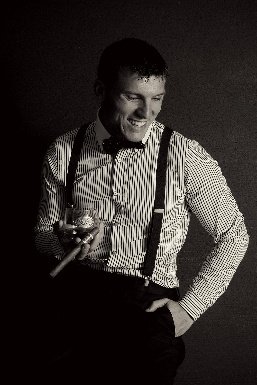 man-holding-scotch-posing-40s-suspenders
