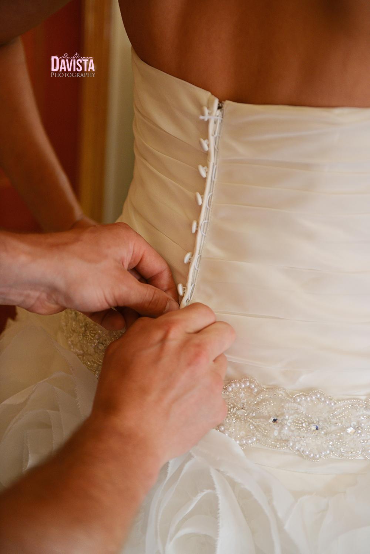 groom zipping up brides dress