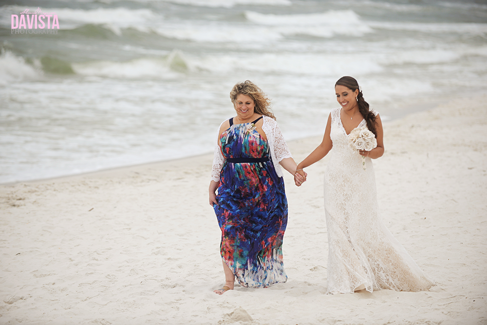 mom and bride walking down the aisle on beach