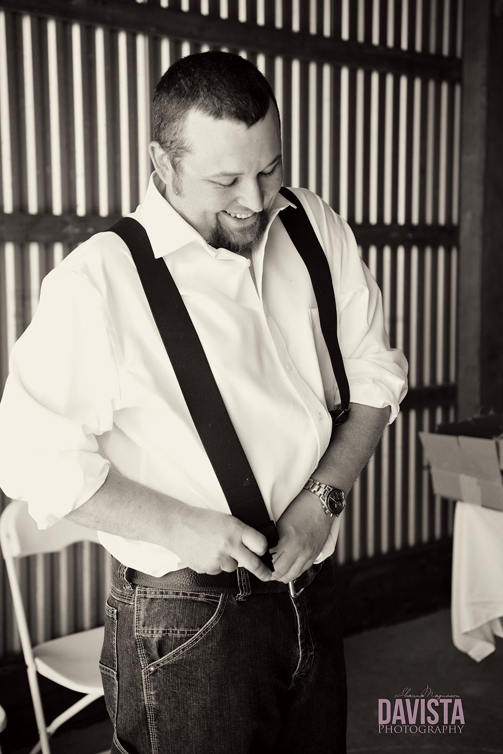 groom getting ready with suspenders