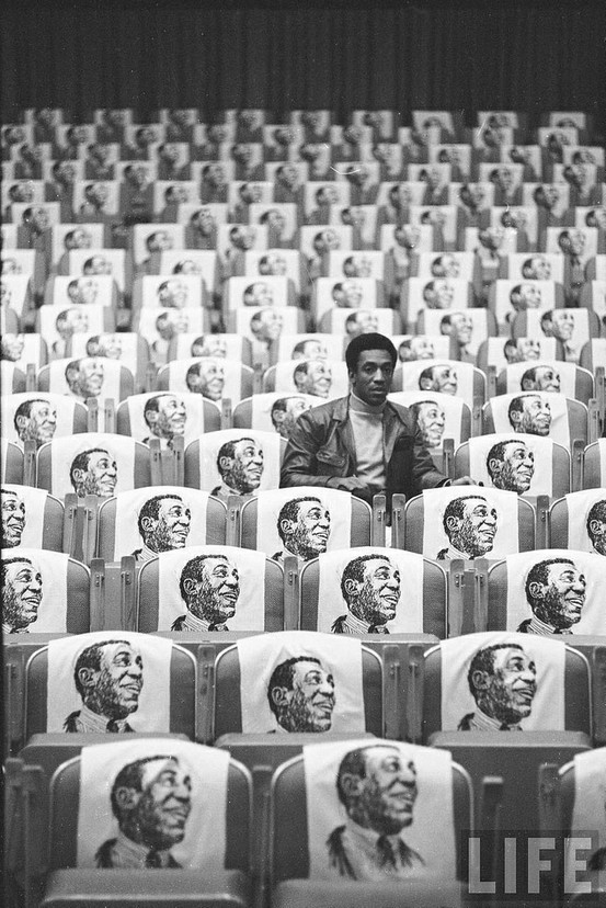 sinuses: Bill Cosby sitting in empty auditorium filled with copies of his likeness on each seat, Las Vegas, 1968. Photo: Michael Rougier