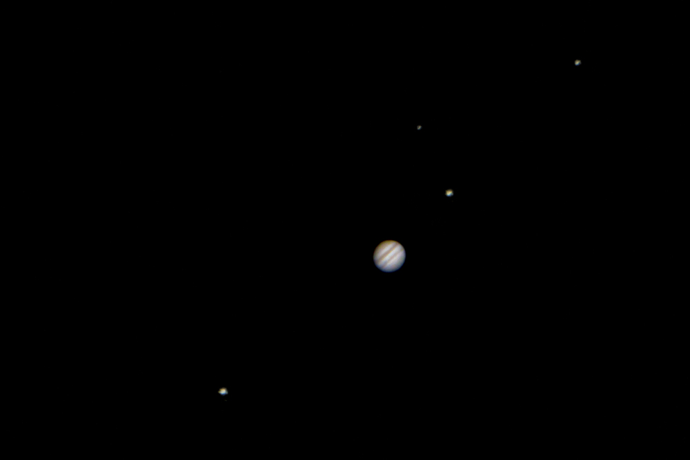 Jupiter, three of its moons on the same plane (from left to right Callisto, Io and Ganymede) and the star HD 49201.