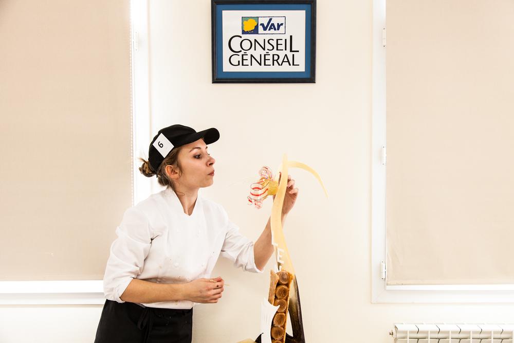 Une candidate fait les finitions de sa pièce en sucre.