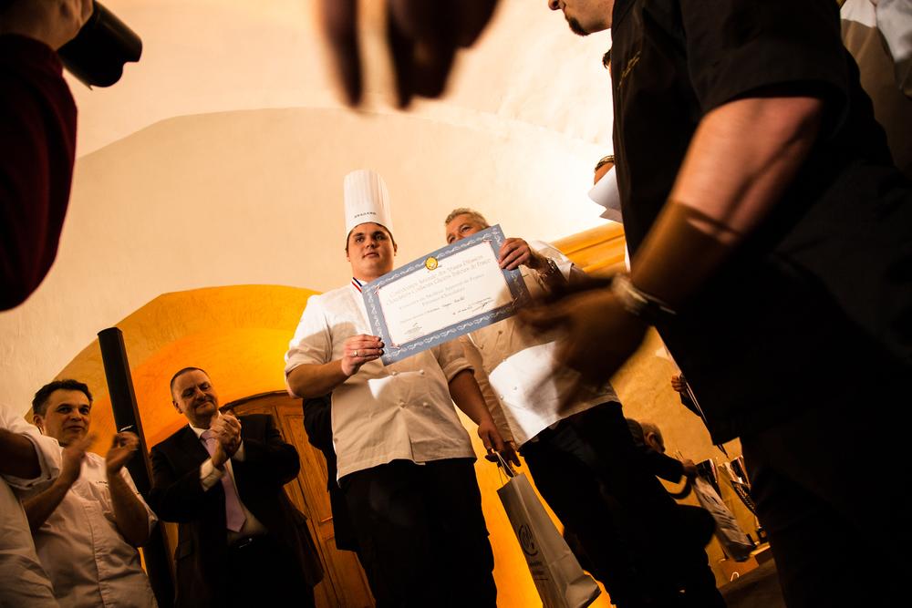 Un des candidats, malchanceux, reçoit un diplôme attestant de sa participation au concours.