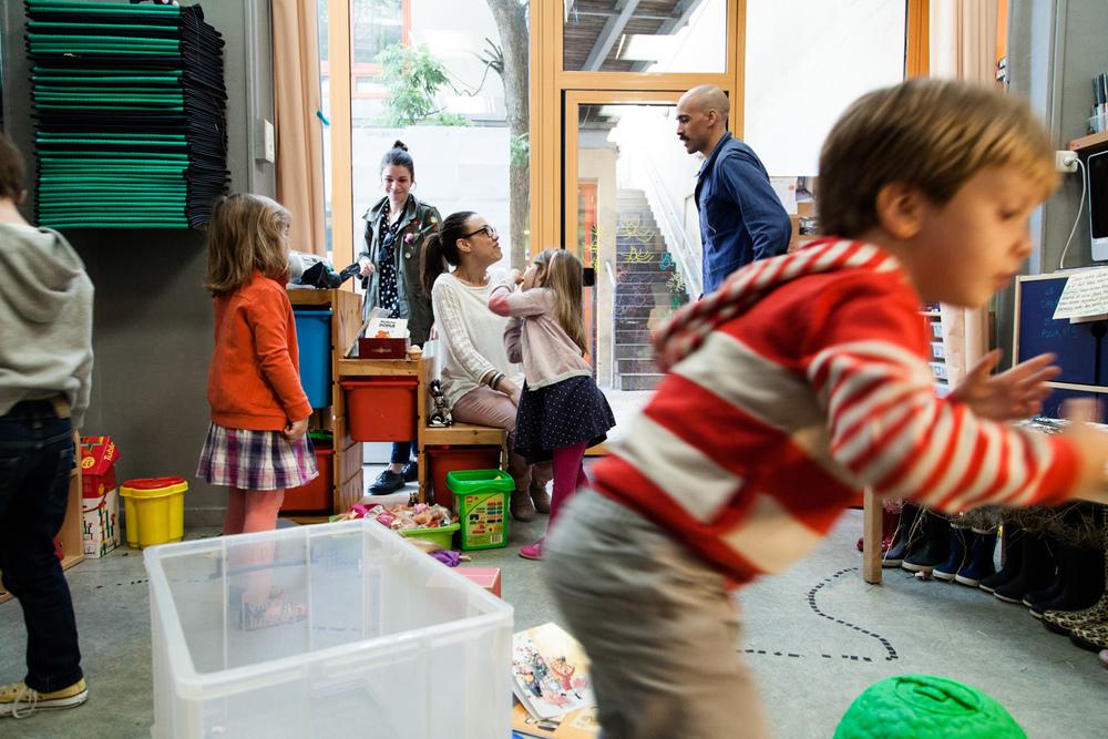 Un père, venu déposer son enfant, discute avec l'institutrice. École aujourd'hui, Paris.  Commande pour Télérama.