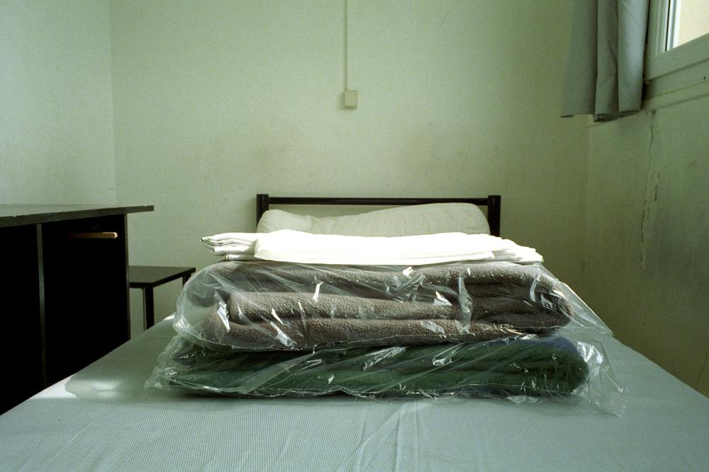 """Un nouvel arrivant découvre sa chambre. Il trouve son trousseau emballé et disposé sur le lit.  Extrait du webdocumentaire   """" Adoma, vers la maison ? """"  , séléctionné au festival Visa Pour l'Image 2009."""