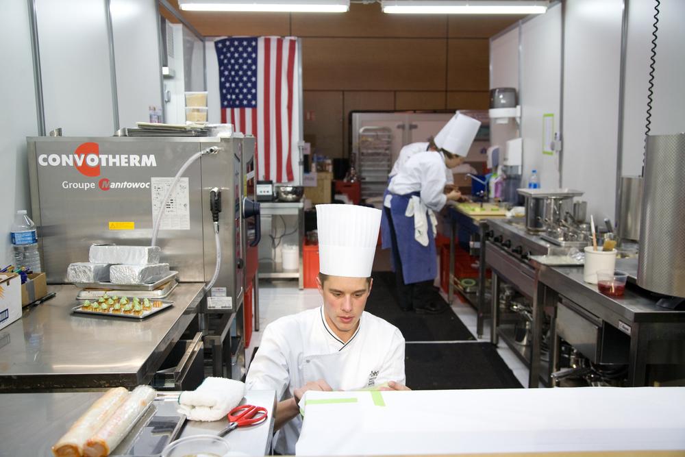 Sur 2 jours, et à partir de 5H30, des équipes de 24 nations, composées du chef, du second de cuisine et d'un commis, s'affrontent dans des boxs reproduisant une cuisine de restaurant.